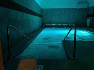 Alkorplan 2000 világosszürke medencefóliával burkolt beltéri úszómedence, nyakmasszázs élményelemmel, RGB színváltós medencelámpával, 365 napos/4 évszakos medencefűtéssel teszi élménnyé a kedves látógatók számára a kikapcsolódást